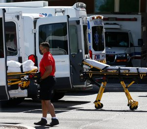 In this June 16, 2020, photo, medical transports and ambulances are parked outside the emergency-room entrance at Banner Desert Medical Center, in Mesa, Ariz. The American Ambulance Association is requesting an additional $2.62 billion in federal COVID-19 relief funds for ambulance services from the Department of Health and Human Services.