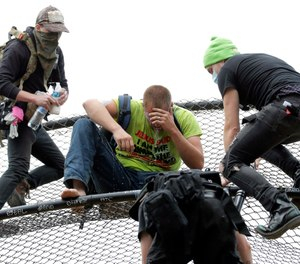 A street preacher, center, is tended to by volunteer medics after he was sprayed with a chemical irritant after he climbed a baseball backstop at Cal Anderson Park, Saturday, June 20, 2020, in the Capitol Hill Occupied Protest zone in Seattle. (AP Photo/Ted S. Warren)