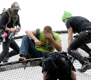 A street preacher, center, is tended to by volunteer medics after he was sprayed with a chemical irritant after he climbed a baseball backstop at Cal Anderson Park, Saturday, June 20, 2020, in the Capitol Hill Occupied Protest zone in Seattle.