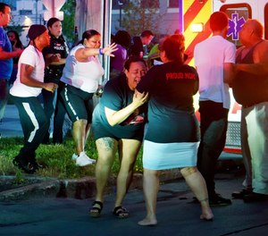 A woman reacts as emergency response crews move wounded people to ambulances after multiple people were shot at a party Saturday, June 20, 2020, in Syracuse, N.Y. (Ellen M. Blalock/Syracuse Post-Standard via AP)