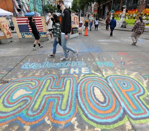 Pedestrians walk Sunday, June 21, 2020, in Seattle, where streets are blocked off in what has been named the Capitol Hill Occupied Protest (CHOP) zone. (AP Photo/Elaine Thompson)