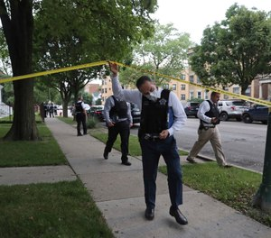 Police detectives canvas the area where a 3-year-old boy was fatally shot while riding in an SUV with his father onSaturday, June 20, 2020, in Chicago. (John J. Kim/Chicago Tribune via AP)