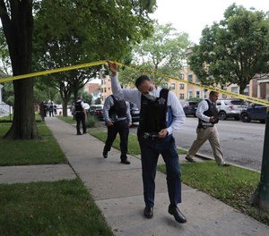 Police detectives canvas the area where a 3-year-old boy was fatally shot while riding in an SUV with his father onSaturday, June 20, 2020, in Chicago.