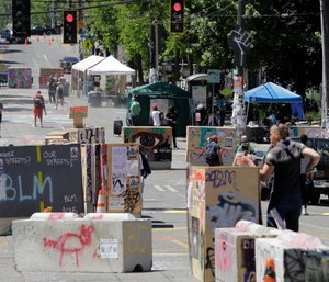 People walk amidst barricades in what has been named the Capitol Hill Occupied Protest zone in Seattle. (AP Photo/Ted S. Warren)