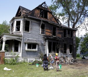 Workers clean up a duplex that was set on fire amid a police investigation scene Tuesday in Milwaukee. (Rick Wood/Milwaukee Journal-Sentinel via AP)