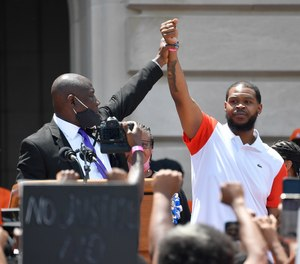 Attorney Benjamin Crump, left, holds up the hand of Kenneth Walker during a rally on the steps of the Kentucky State Capitol in Frankfort, Ky., Thursday, June 25, 2020.