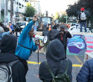 A man urges protesters not to be violent after workers and heavy equipment from the Seattle Department of Transportation arrived at the the CHOP (Capitol Hill Occupied Protest) zone in Seattle, Friday, June 26. (AP Photo/Ted S. Warren)