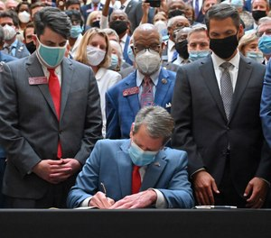 Gov. Brian Kemp, center, signs a bill into law on the last day of the legislative session at Georgia State Capitol, Friday, June 26, 2020. (Alyssa Pointer/Atlanta Journal-Constitution via AP)