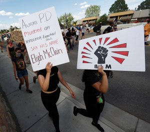 Protesters carry placards during a rally and march over the death of 23-year-old Elijah McClain, Saturday, June 27, 2020, outside the police department in Aurora, Colo.