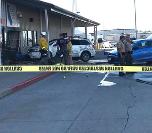 Deputies and firefighters stand outside the Red Bluff Walmart distribution center after a man reportedly opened fire there and rammed his vehicle into the building, Saturday, June 27, 2020, in Red Bluff, Calif.
