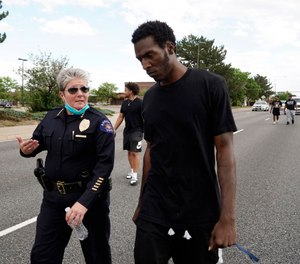 Interim Aurora Police Chief Vanessa Wilson and Jay B. confer as protesters march north on South Chambers Road during a peaceful protest against police brutality following the death of George Floyd in Aurora, Colo. (Photo/Philip B. Poston of The Aurora Sentinel via AP)