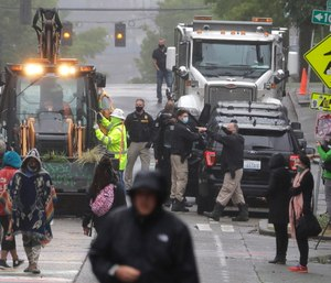 Seattle Police, at right, look on as Department of Transportation workers remove barricades at the intersection of 10th Ave. and Pine St. at the CHOP (Capitol Hill Occupied Protest) zone in Seattle. (AP Photo/Ted S. Warren)
