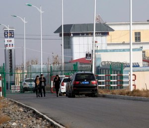 People walk by a police station by the front gate of the Artux City Vocational Skills Education Training Service Center in Artux in western China's Xinjiang region.