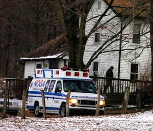 An ambulance is parked outside the farmhouse where Kenzie Marie Houk was killed in Wampum, Pa.