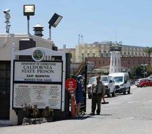 A Department of Corrections officer guards the main entryway leading into San Quentin State Prison in San Quentin, Calif. (AP Photo/Eric Risberg)