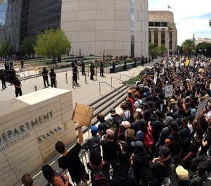 In this June 2, 2020, file photo, demonstrators kneel in front of LAPD headquarters during a protest in Los Angeles over the death of George Floyd. (AP Photo/Mark J. Terrill, File)