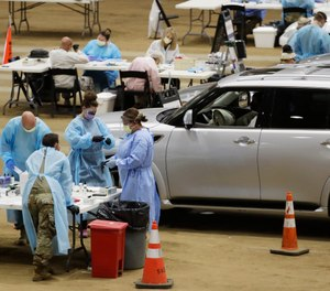 Workers administer COVID-19 tests at a drive-through facility set up in the Williamson County Agricultural Center, Thursday, July 2, 2020, in Franklin, Tenn. Confirmed COVID-19 cases have risen in 40 of 50 states over the past few weeks. (AP Photo/Mark Humphrey)