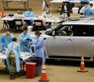 Workers administer COVID-19 tests at a drive-through facility set up in the Williamson County Agricultural Center, Thursday, July 2, 2020, in Franklin, Tenn. Confirmed COVID-19 cases have risen in 40 of 50 states over the past few weeks.