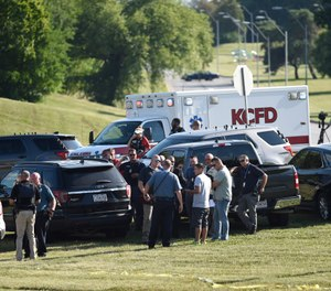 Law enforcement agents confer near the site of a shooting Thursday, July 2, 2020, in Kansas City, Mo. The shooting left a suspect dead and a police officer in critical condition after being shot in the head.(Tammy Ljungblad/The Kansas City Star via AP)