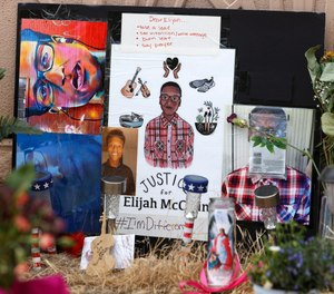 A makeshift memorial stands at a site across the street from where Elijah McClain was stopped by Aurora, Colo., Police Department officers. The Colorado Department of Public Health and Environment has announced it is reopening its investigation into the use of ketamine to sedate McClain during his arrest.