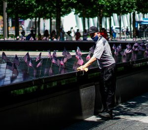 A worker disinfects the area of one of the reflecting pools at the 9/11 Memorial Plaza on July 4, 2020. The Tunnel to Towers Foundation is planning an in-person, socially distanced name-reading ceremony with the families of 9/11 victims in lieu of the official in-person ceremony, which was canceled due to the COVID-19 pandemic. (AP Photo/Eduardo Munoz Alvarez)