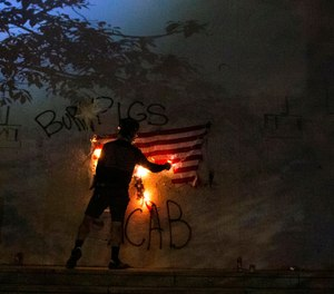 Protesters burn a U.S. flag in downtown Portland, Ore. on July 4, 2020. (Beth Nakamura/The Oregonian via AP, File)