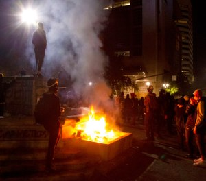 Protesters gather near a fire in downtown Portland, Ore. on July 4, 2020. (Beth Nakamura/The Oregonian via AP, File)