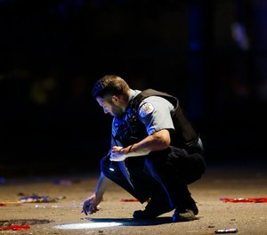 An officer investigates the scene of a shooting in Chicago on July 5, 2020.