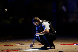In this July 5, 2020, photo, an officer investigates the scene of a shooting in Chicago. Still reeling from the coronavirus pandemic and street protests over the police killing of Floyd, exhausted cities around the nation are facing yet another challenge: A surge in recent shootings has left dozens dead, including young children. Image: Armando L. Sanchez/Chicago Tribune via AP