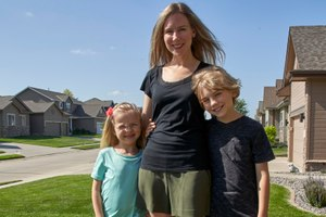Tara Carlson poses for a photo with her children Kyler, 9, and Alayna, 6, outside their home in Omaha, Neb., Tuesday, July 7, 2020. Carlson pulled her kids out of summer camp at the last minute, losing $300 in deposits. Image: AP Photo/Nati Harnik