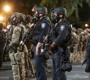 Agents from different components of the Department of Homeland Security are deployed to protect a federal courthouse in Portland, Ore., on Sunday, July 5, 2020.  (Doug Brown via AP)