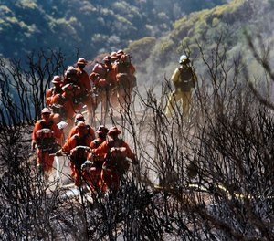 This Dec. 19, 2017 photo shows members of an inmate firefighting hand crew hiking on their way to work near Montecito, Calif. An inmate firefighter who was injured battling the Zogg Fire faces deportation to Laos due to his criminal convictions.