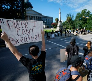 Demonstrators protest in front of a confederate statue at the State House on Friday, July 10, 2020, in Columbia, S.C. (AP Photo/Chris Carlson)