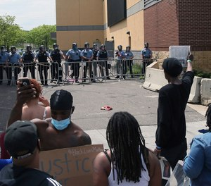 In this May 27, 2020, file photo, a protester holds a newspaper in front of the Minneapolis police standing guard against protesters at the Third Precinct as people protest the arrest and death of George Floyd. (AP Photo/Jim Mone, File)