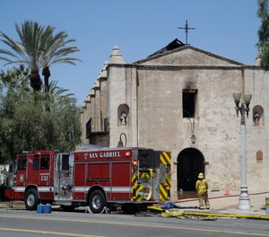 A firefighter stands outside the San Gabriel Mission in the aftermath of a fire, Saturday, July 11, 2020, in San Gabriel, Calif. The fire destroyed the rooftop and most of the interior of the nearly 250-year-old California church that was undergoing renovation. (AP Photo/Marcio Jose Sanchez)