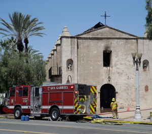 A firefighter stands outside the San Gabriel Mission in the aftermath of a fire, Saturday, July 11, 2020, in San Gabriel, Calif. The fire destroyed the rooftop and most of the interior of the nearly 250-year-old California church that was undergoing renovation.