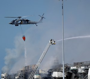 A helicopter drops water on the USS Bonhomme Richard as crews fight the fire Monday, July 13, 2020, in San Diego. The fire and an explosion on the ship have injured at least 59 people, including 36 sailors. (AP Photo/Gregory Bull)