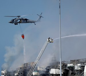 A helicopter drops water on the USS Bonhomme Richard as crews fight the fire Monday, July 13, 2020, in San Diego. The fire and an explosion on the ship have injured at least 59 people, including 36 sailors.