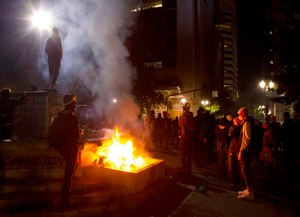 In this July 4, 2020, photo, protesters gather near a fire in downtown Portland, Ore. Oregon's largest city is in crisis as violent protests have wracked downtown for weeks. Image: Beth Nakamura/The Oregonian via AP