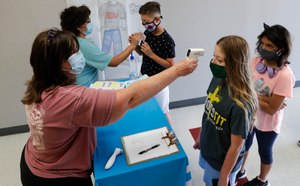 Amid concerns of the spread of COVID-19, science teachers Ann Darby, left, and Rosa Herrera check-in students before a summer STEM camp at Wylie High School Tuesday, July 14, 2020, in Wylie, Texas. Image: AP Photo/LM Otero