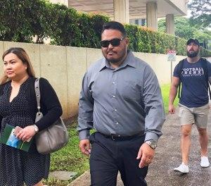 In this Sept. 25, 2019 file photo, former Honolulu police officer Reginald Ramones, center, walks down a street in Honolulu. (AP Photo/Jennifer Sinco Kelleher, File)