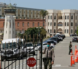 In this July 9, 2020, file photo, a correctional officer closes the main gate at San Quentin State Prison in San Quentin, Calif. (AP Photo/Eric Risberg, File)
