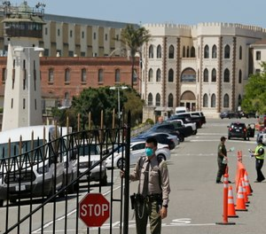 A correctional officer closes the main gate at San Quentin State Prison in San Quentin, Calif. (AP Photo/Eric Risberg)