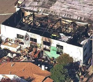 This Dec. 3, 2016, image shows the Ghost Ship Warehouse after a fire swept through the building in Oakland, Calif. Oakland will pay $32.7 million to settle lawsuits filed over the fire that killed 36 people at an illegally converted warehouse.