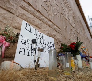 In this July 3, 2020, file photo, a memorial site across the street from where Elijah McClain was stopped by Aurora, Colo. (AP Photo/David Zalubowski, File)