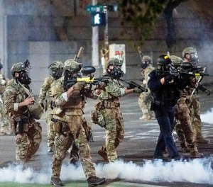 In this July 20, 2020 file photo Federal agents use crowd control munitions to disperse protesters at the Mark O. Hatfield United States Courthouse in Portland, Ore.