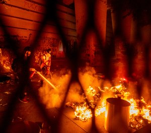 A protester extinguishes a fire set by fellow protesters at the Mark O. Hatfield United States Courthouse on Wednesday, July 22, 2020, in Portland, Ore.