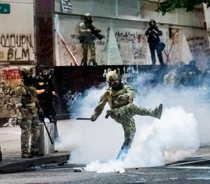 Federal officers use crowd control munitions to disperse protesters outside the Mark O. Hatfield United States Courthouse on Tuesday, July 21, 2020, in Portland, Ore. (AP Photo/Noah Berger)