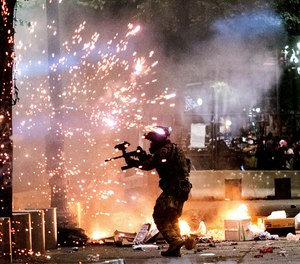 A federal officer fires crowd control munitions at protesters on Friday, July 24, 2020, in Portland, Ore.  (AP Photo/Noah Berger)