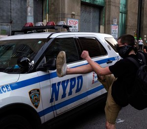 A protester kicks a police vehicle in an attempt to break its side mirror during a protest Saturday, July 25, 2020, in New York. (AP Photo/Yuki Iwamura)